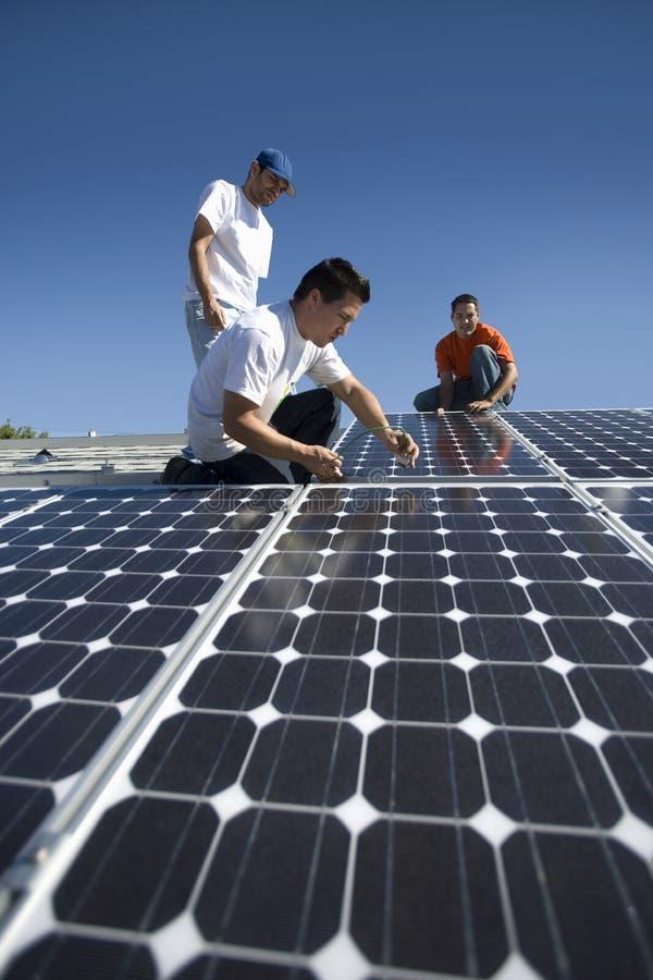 Μηχανικοί που εργάζονται στο ηλιακό πλαίσιο ενάντια στον ουρανό στοκ φωτογραφία με δικαίωμα ελεύθερης χρήσης