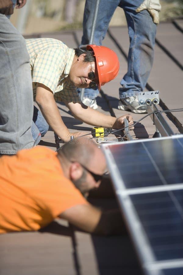 Μηχανικοί που εργάζονται στο ηλιακό πλαίσιο στη στέγη στοκ φωτογραφία με δικαίωμα ελεύθερης χρήσης