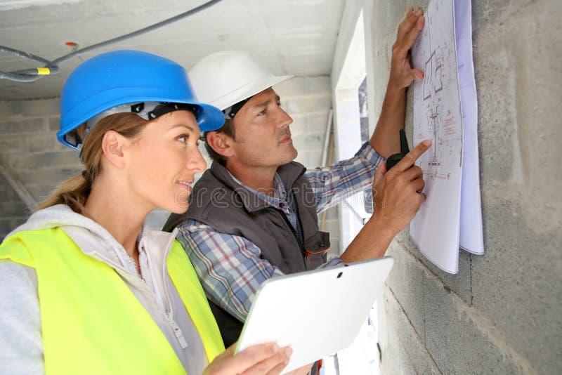 Μηχανικοί που εργάζονται στο σχεδιάγραμμα στο εργοτάξιο στοκ φωτογραφίες