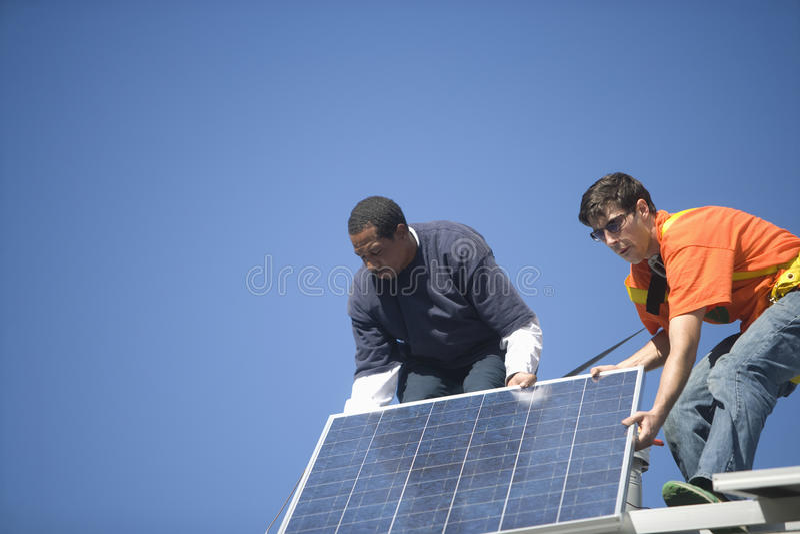 Μηχανικοί που καθορίζουν το ηλιακό πλαίσιο ενάντια στο μπλε ουρανό στοκ φωτογραφία