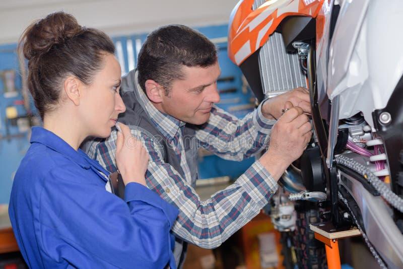 Μηχανικοί που καθορίζουν motocycle στο γκαράζ στοκ φωτογραφία με δικαίωμα ελεύθερης χρήσης