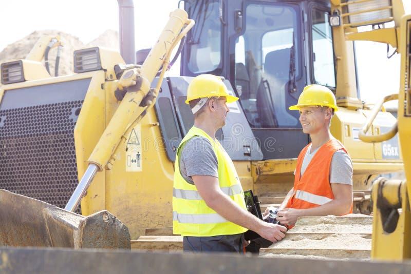 Μηχανικοί που συζητούν στο εργοτάξιο οικοδομής στοκ φωτογραφίες