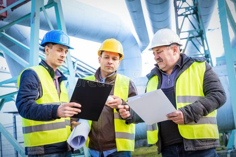Μηχανικοί που συζητούν τη συντήρηση ενός εργοστασίου πετροχημικών στοκ εικόνα