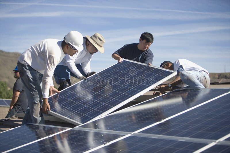 Μηχανικοί που τοποθετούν τα ηλιακά πλαίσια στη στέγη στοκ φωτογραφία με δικαίωμα ελεύθερης χρήσης