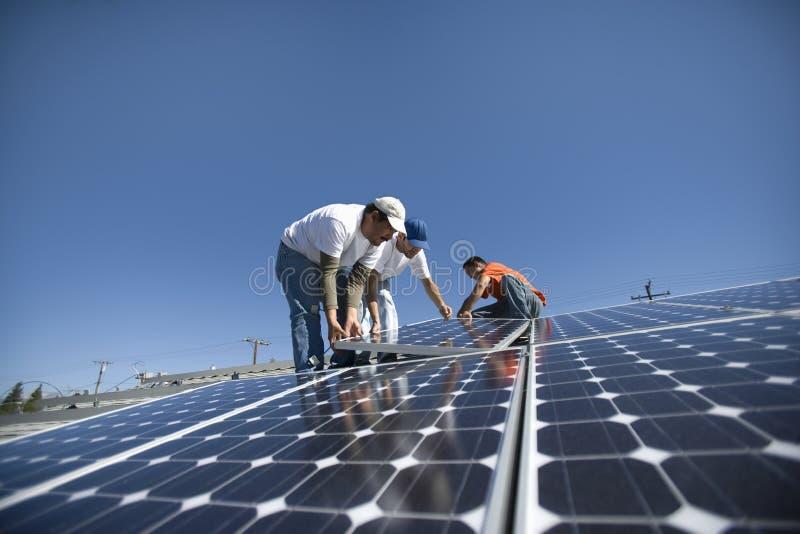 Μηχανικοί που τοποθετούν το ηλιακό πλαίσιο ενάντια στον ουρανό στοκ εικόνες με δικαίωμα ελεύθερης χρήσης