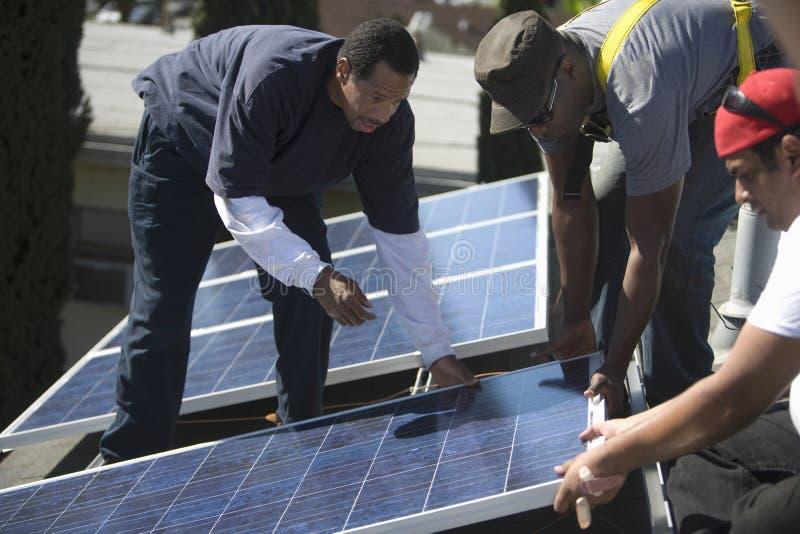 Μηχανικοί που τοποθετούν το ηλιακό πλαίσιο μαζί στη στέγη στοκ εικόνα με δικαίωμα ελεύθερης χρήσης