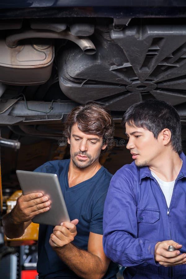 Μηχανικοί που χρησιμοποιούν την ψηφιακή ταμπλέτα κάτω από το ανυψωμένο αυτοκίνητο στοκ φωτογραφίες