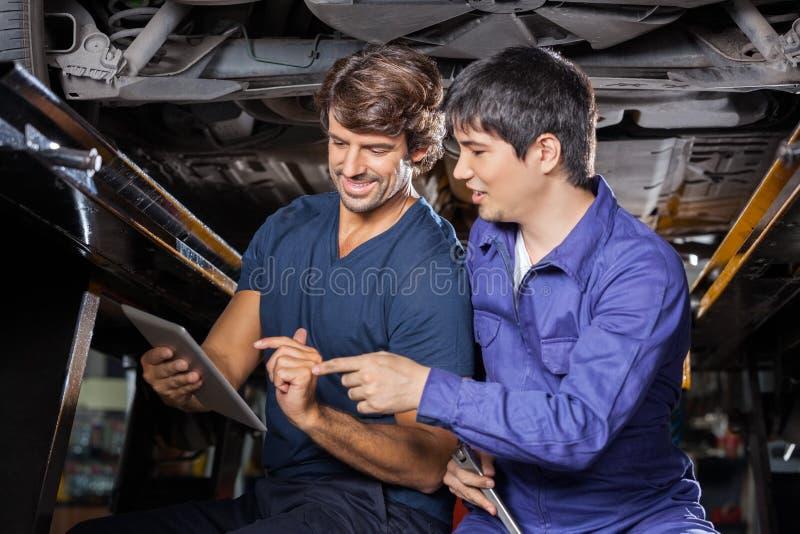 Μηχανικοί που χρησιμοποιούν τον υπολογιστή ταμπλετών κάτω από το ανυψωμένο αυτοκίνητο στοκ φωτογραφία με δικαίωμα ελεύθερης χρήσης