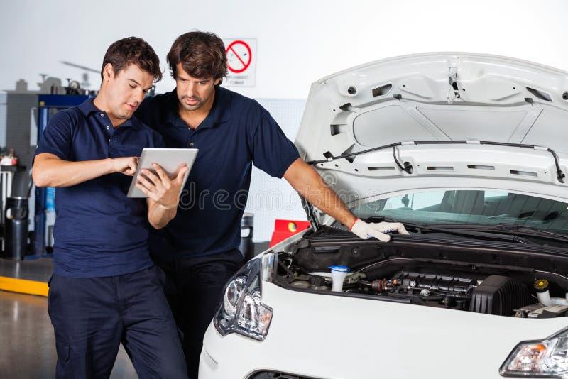 Μηχανικοί που χρησιμοποιούν τον υπολογιστή ταμπλετών με το χαλασμένο αυτοκίνητο στοκ εικόνες με δικαίωμα ελεύθερης χρήσης