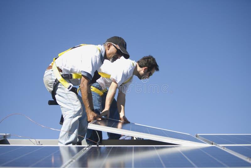 Μηχανικοί Multiethnic που τοποθετούν το ηλιακό πλαίσιο ενάντια στον ουρανό στοκ φωτογραφία με δικαίωμα ελεύθερης χρήσης