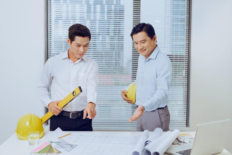 Μηχανικός αρχιτεκτόνων που συζητά στον πίνακα με το σχεδιάγραμμα του AR στοκ εικόνα