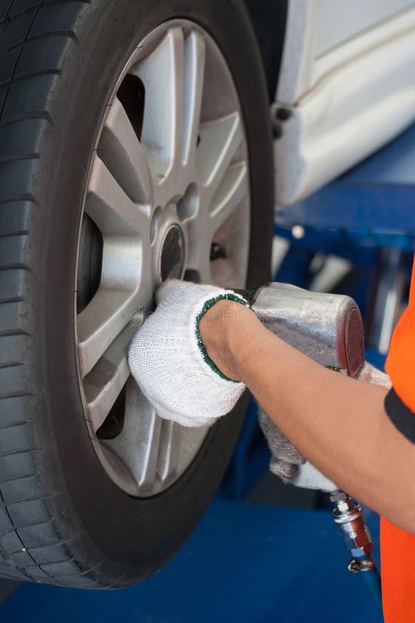 Μηχανικός αυτοκινήτων που βιδώνει ή που ξεβιδώνει τη ρόδα αυτοκινήτων του ανυψωμένου automobi στοκ εικόνα