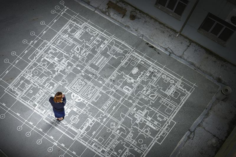 Μηχανικός γυναικών που σκέφτεται πέρα από το σχέδιό του Μικτά μέσα στοκ φωτογραφία με δικαίωμα ελεύθερης χρήσης