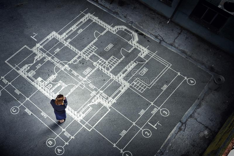 Μηχανικός γυναικών που σκέφτεται πέρα από το σχέδιό του Μικτά μέσα στοκ φωτογραφία