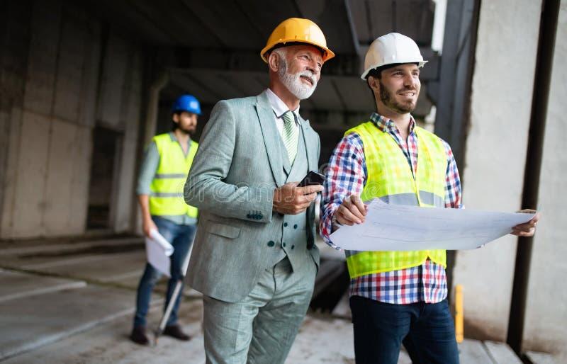 Μηχανικός, επιστάτης και εργαζόμενος που συζητούν στην οικοδόμηση του εργοτάξιου οικοδομής στοκ φωτογραφίες