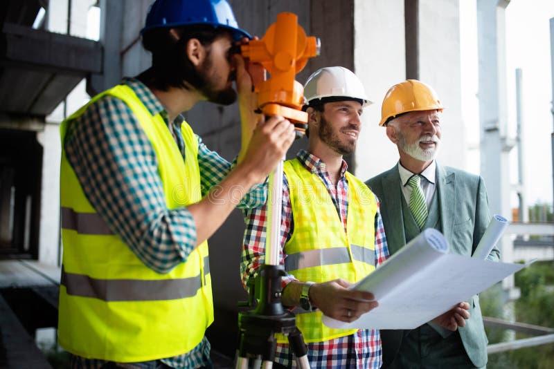 Μηχανικός, επιστάτης και εργαζόμενος που συζητούν στην οικοδόμηση του εργοτάξιου οικοδομής στοκ εικόνες