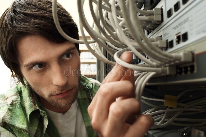 Μηχανικός δικτύων που εργάζεται στο δωμάτιο κεντρικών υπολογιστών στοκ εικόνες