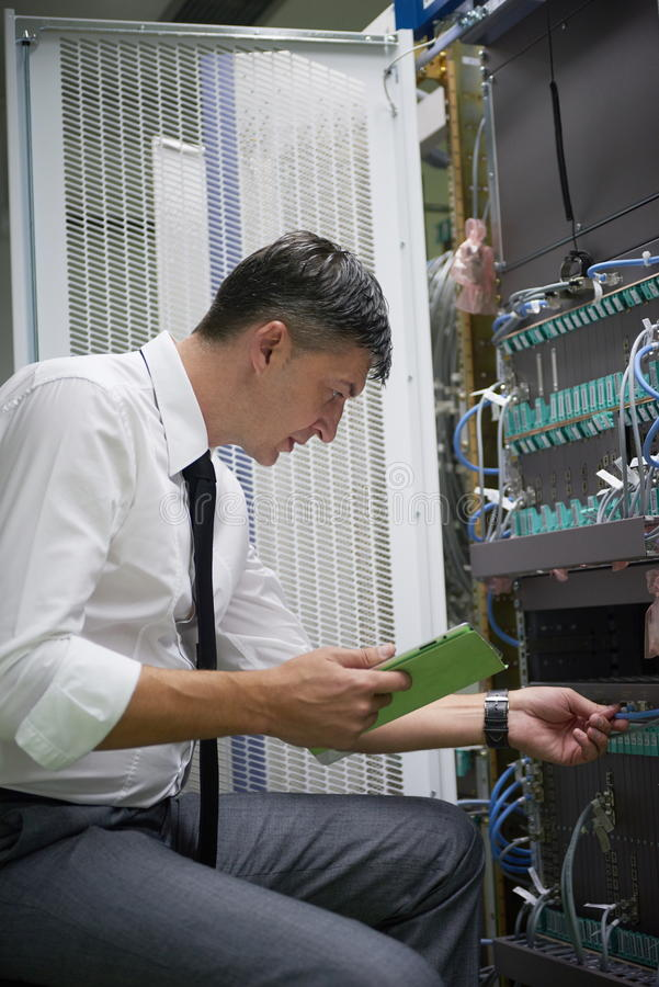 Μηχανικός δικτύων που εργάζεται στο δωμάτιο κεντρικών υπολογιστών στοκ φωτογραφίες