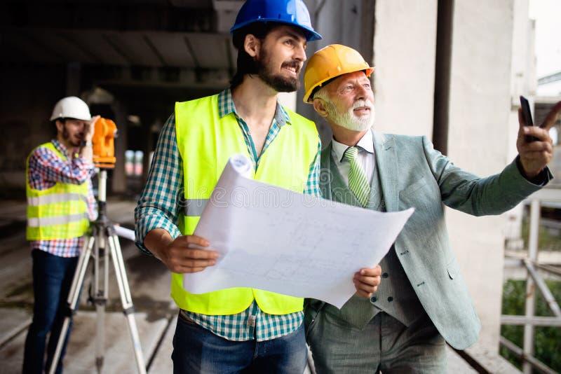 Μηχανικός και διευθυντής εργοτάξιων οικοδομής που εξετάζουν τα σχεδιαγράμματα και τα σχέδια στοκ εικόνα