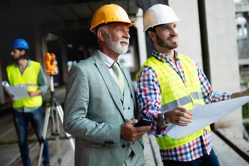 Μηχανικός και διευθυντής εργοτάξιων οικοδομής που εξετάζουν τα σχεδιαγράμματα και τα σχέδια στοκ φωτογραφία με δικαίωμα ελεύθερης χρήσης