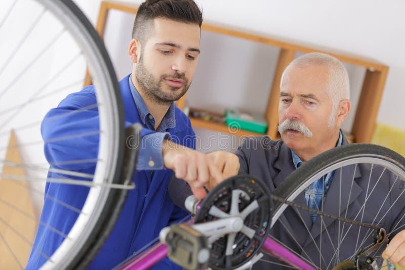 Μηχανικός και εκπαιδευόμενος ποδηλάτων που εργάζονται στο ποδήλατο στοκ εικόνες με δικαίωμα ελεύθερης χρήσης