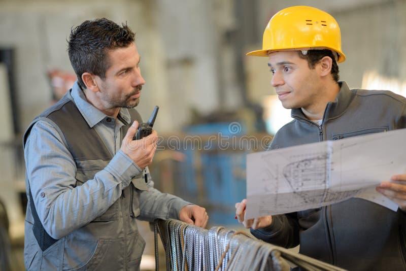 Μηχανικός και εργαζόμενος που ελέγχουν το σχέδιο στο εργοτάξιο οικοδομής στοκ εικόνες
