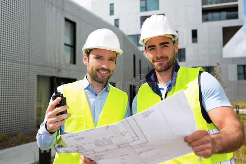 Μηχανικός και εργαζόμενος που ελέγχουν το σχέδιο στο εργοτάξιο οικοδομής στοκ εικόνες με δικαίωμα ελεύθερης χρήσης