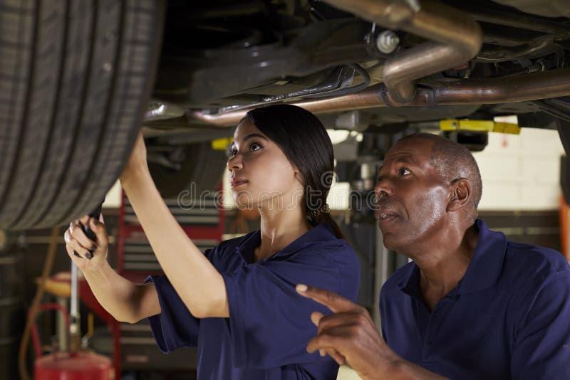Μηχανικός και θηλυκός εκπαιδευόμενος που εργάζεται κάτω από το αυτοκίνητο από κοινού στοκ εικόνα
