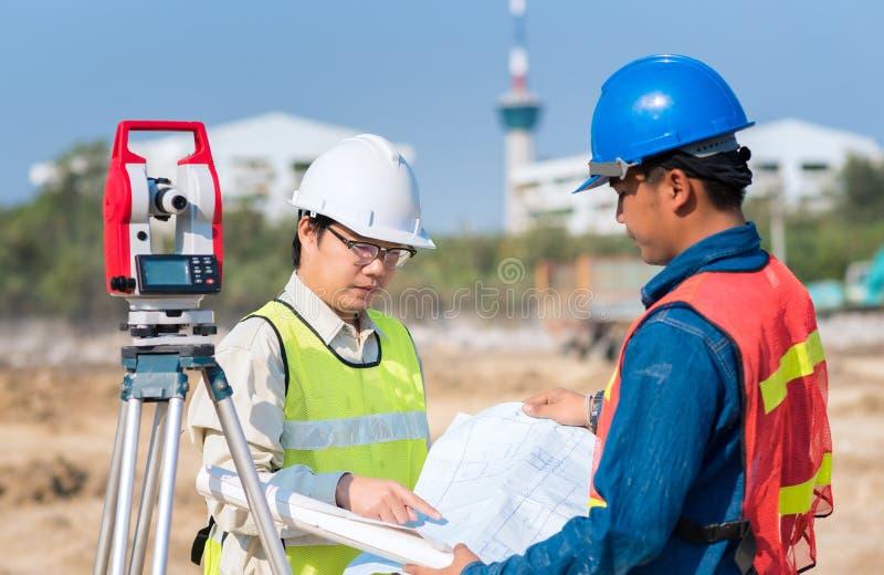 Μηχανικός κατασκευής και εργαζόμενος επιστατών που ελέγχει την περιοχή στοκ εικόνα