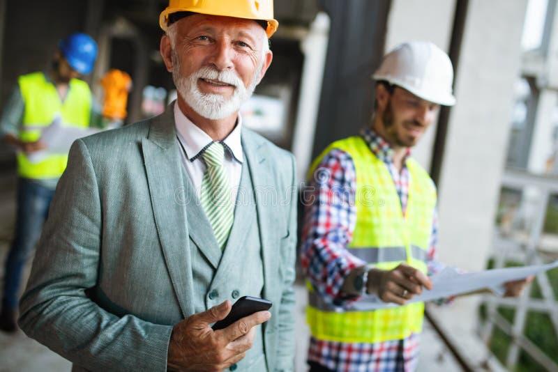 Μηχανικός κατασκευής με τον εργαζόμενο επιστατών που ελέγχει το εργοτάξιο οικοδομής στοκ εικόνες με δικαίωμα ελεύθερης χρήσης
