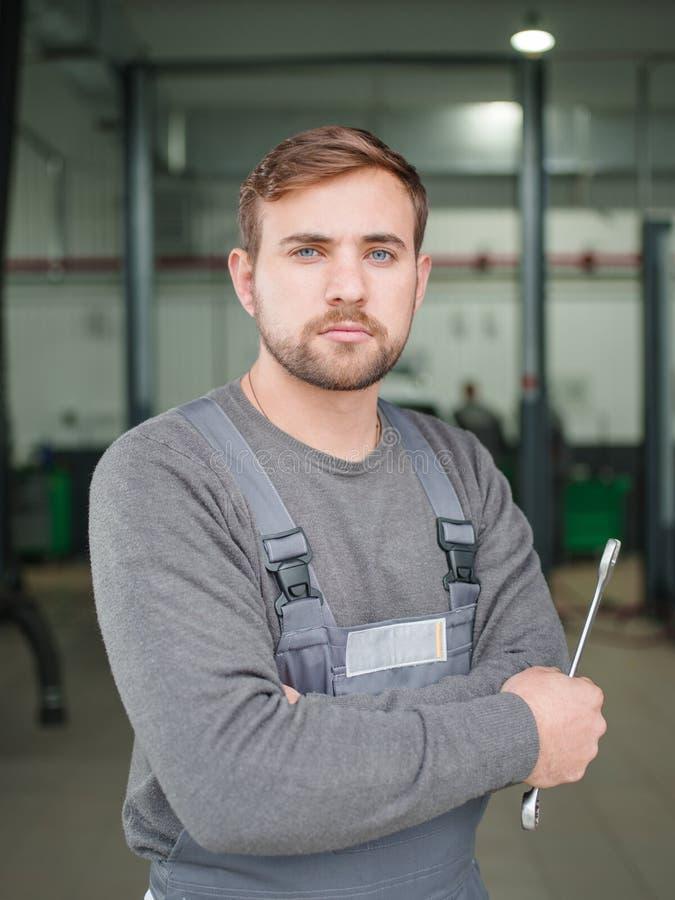 Μηχανικός με τα κλειδιά στην κινηματογράφηση σε πρώτο πλάνο εργαστηρίων ενάντια στον τοίχο στοκ φωτογραφία με δικαίωμα ελεύθερης χρήσης