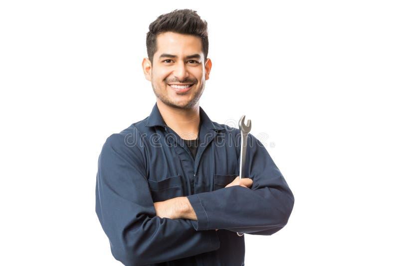 Μηχανικός με τα μόνιμα χέρια γαλλικών κλειδιών που διπλώνονται στο άσπρο υπόβαθρο στοκ εικόνες