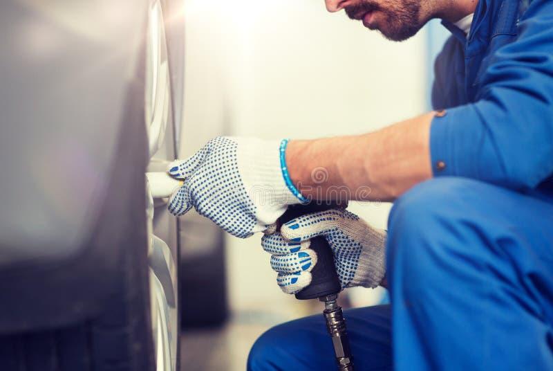 Μηχανικός με τη μεταβαλλόμενη ρόδα αυτοκινήτων κατσαβιδιών στοκ φωτογραφίες