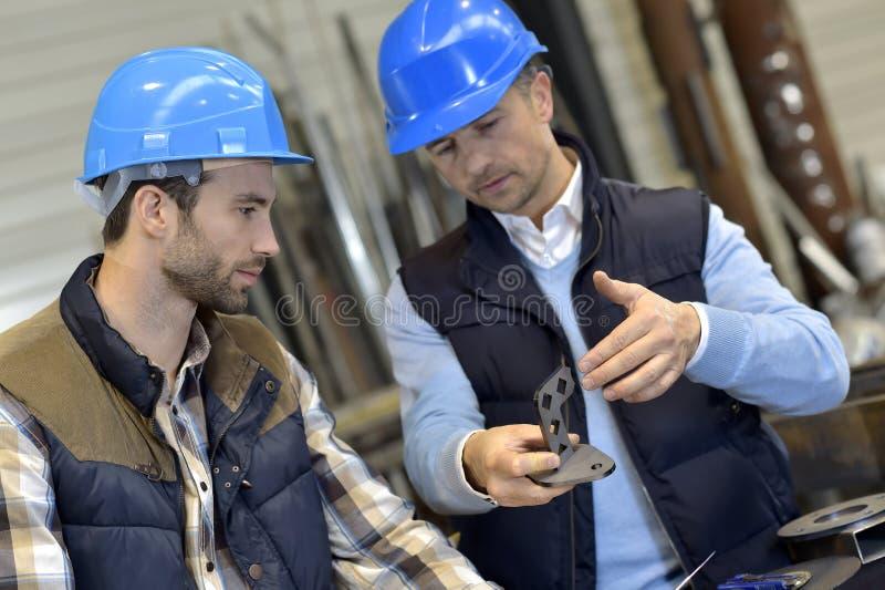 Μηχανικός με το μηχανικό εργαζόμενο που ελέγχει στα ποιοτικά προϊόντα στοκ εικόνα
