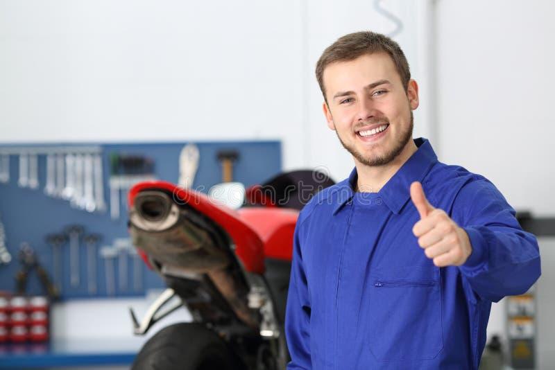 Μηχανικός μοτοσικλετών με τον αντίχειρα επάνω σε ένα εργαστήριο στοκ φωτογραφία