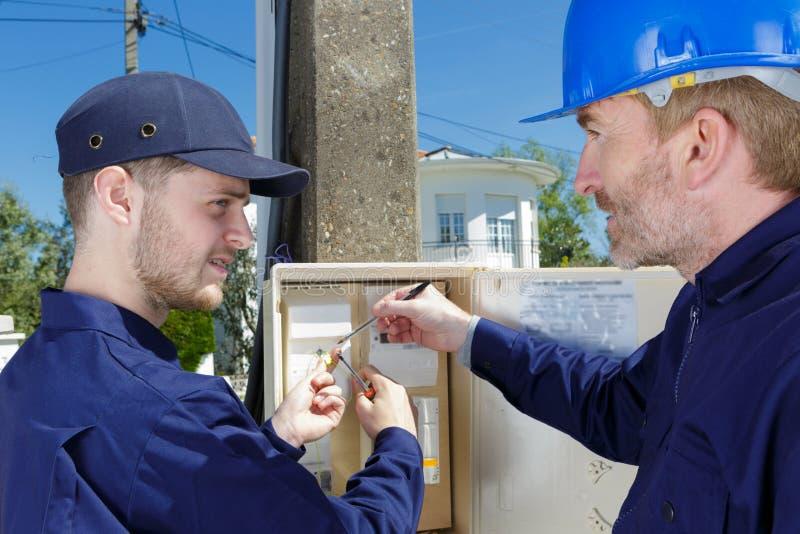Μηχανικός οικοδόμων ηλεκτρολόγων που ελέγχει τα στοιχεία από το πίνακα ελέγχου στοκ εικόνα με δικαίωμα ελεύθερης χρήσης