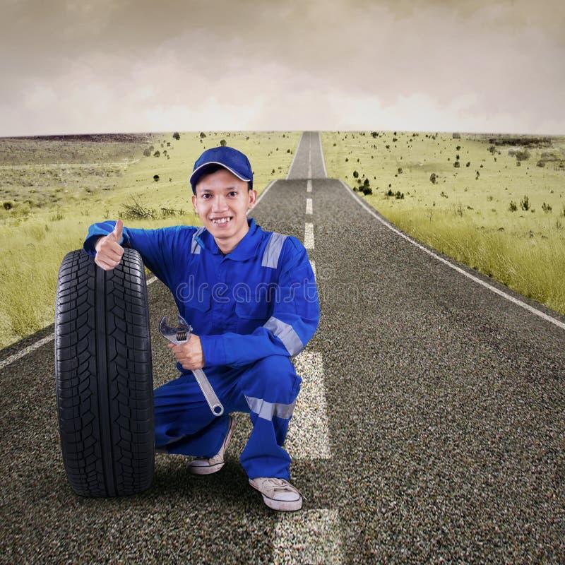 Μηχανικός παρουσιάζοντας αντίχειρας επάνω στο δρόμο στοκ εικόνα