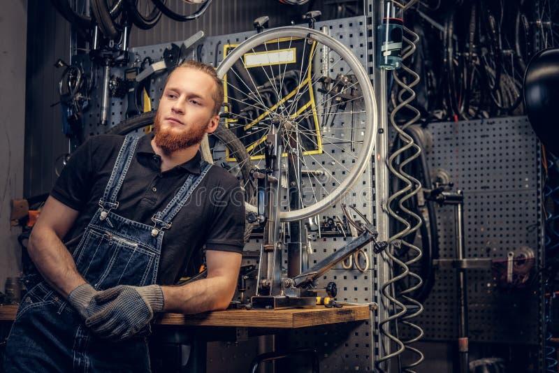 Μηχανικός ποδηλάτων σε ένα εργαστήριο με τα μέρη ποδηλάτων και ρόδα σε ένα υπόβαθρο στοκ φωτογραφίες με δικαίωμα ελεύθερης χρήσης