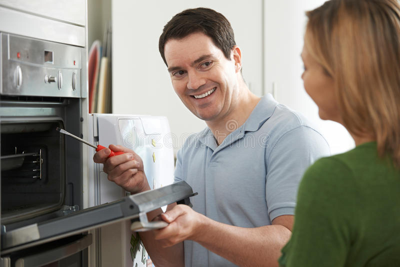 Μηχανικός που δίνει τις συμβουλές γυναικών για την επισκευή κουζινών στοκ εικόνα