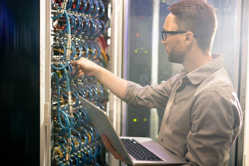 Μηχανικός που αναλύει τις συνδέσεις κεντρικών υπολογιστών στοκ φωτογραφία με δικαίωμα ελεύθερης χρήσης