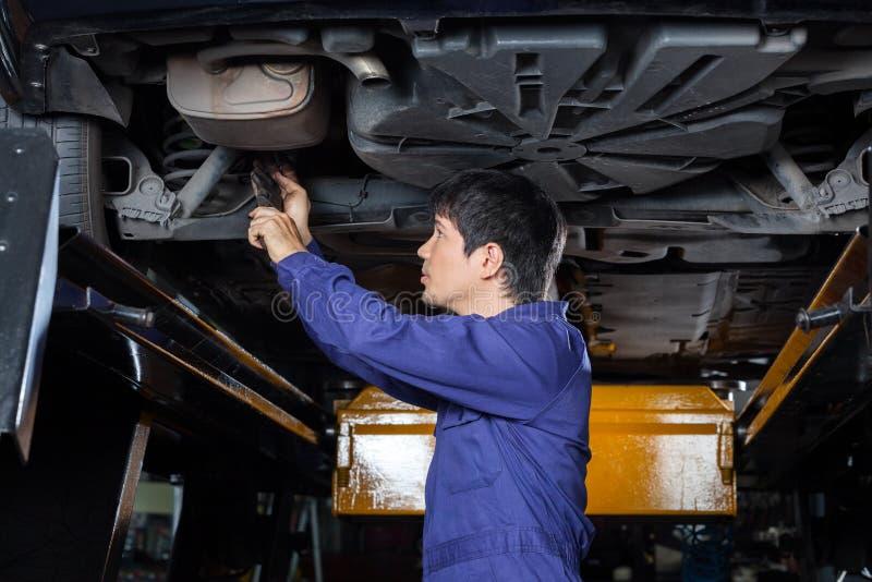 Μηχανικός που εξετάζει κάτω από το ανυψωμένο αυτοκίνητο στοκ φωτογραφία με δικαίωμα ελεύθερης χρήσης