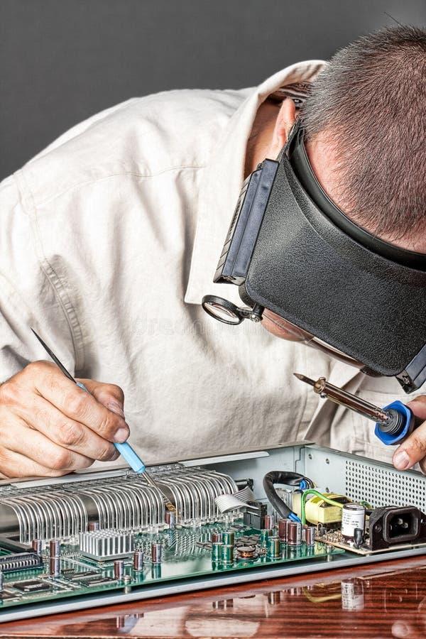 Μηχανικός που επισκευάζει το χαρτόνι κυκλωμάτων στοκ εικόνα με δικαίωμα ελεύθερης χρήσης