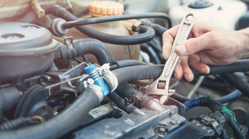 Μηχανικός που εργάζεται στην αυτόματη επισκευή Χέρι του μηχανικού αυτοκινήτων με το γαλλικό κλειδί στοκ εικόνες