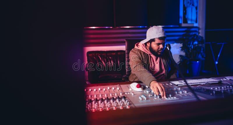 Μηχανικός που εργάζεται στον ήχο που αναμιγνύει το γραφείο στο στούντιο καταγραφής στοκ εικόνες