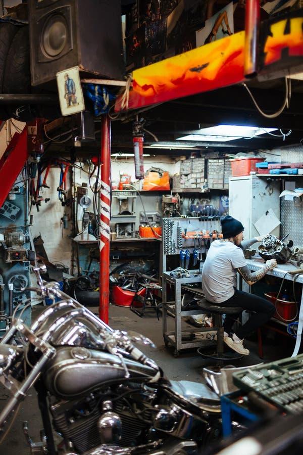 Μηχανικός που εργάζεται στο γκαράζ μοτοσικλετών στοκ εικόνα
