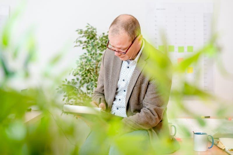 Μηχανικός που κάνει τα σχέδια για το σημειωματάριο στον εργασιακό χώρο στοκ φωτογραφίες