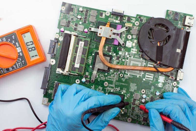 Μηχανικός που καθορίζει το σπασμένο υπολογιστή στην εργασία στοκ φωτογραφίες