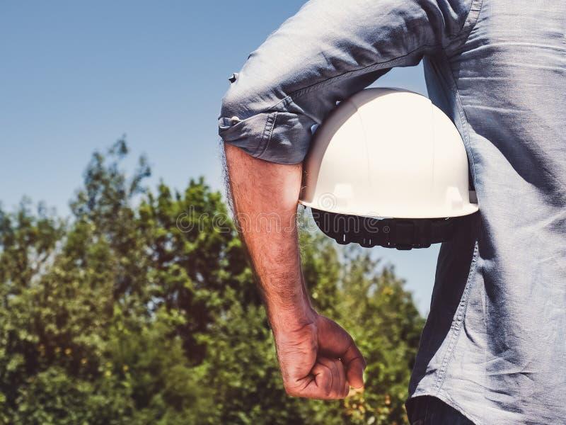 Μηχανικός, που κρατά άσπρο hardhat στο πάρκο στοκ εικόνες με δικαίωμα ελεύθερης χρήσης