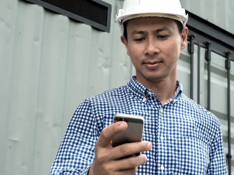 Μηχανικός που κρατά το κινητό τηλέφωνο, πολυάσχολος ανάδοχος κτηρίου στην εργασία στοκ εικόνες