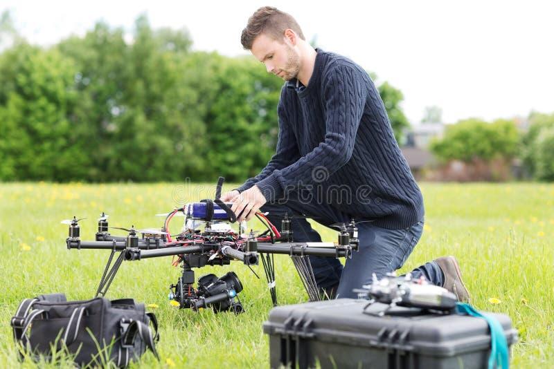 Μηχανικός που προετοιμάζει τον κηφήνα επιτήρησης στο πάρκο στοκ εικόνα με δικαίωμα ελεύθερης χρήσης